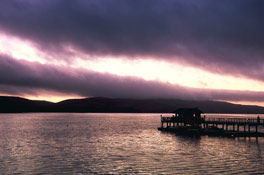 sunset and clouds behind dock at nick's cove