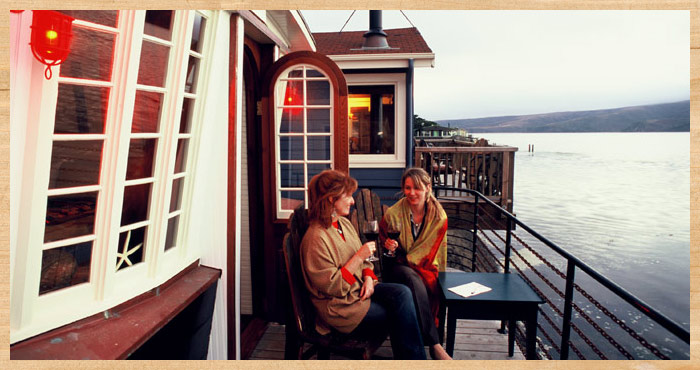 Two women on the deck of the Nicolina waterfront cottage at Nick's Cove on Tomalas Bay just north of San Francisco